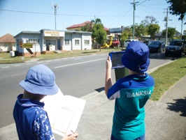 2 students working together on a suburban street studying history