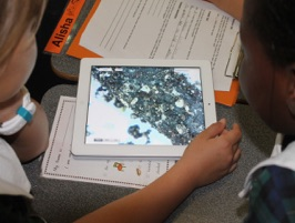 image of students looking at soil on ipad